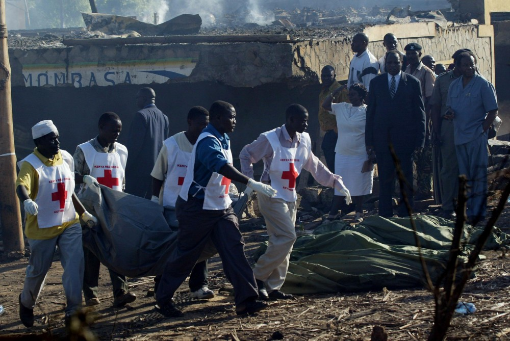 MOMBASA, KENYA:  Kenyan Red Cross volunteers carry the body of one of the victims of the Paradise Hotel bomb blast in  Mombasa 28 November 2002. Thirteen people including the attackers, were killed at the Israeli-owned hotel in a suicide bombing that targeted a package tour group organized by the Paradise Geographic agency. AFP PHOTO/Pedro UGARTE (Photo credit should read PEDRO UGARTE/AFP/Getty Images)