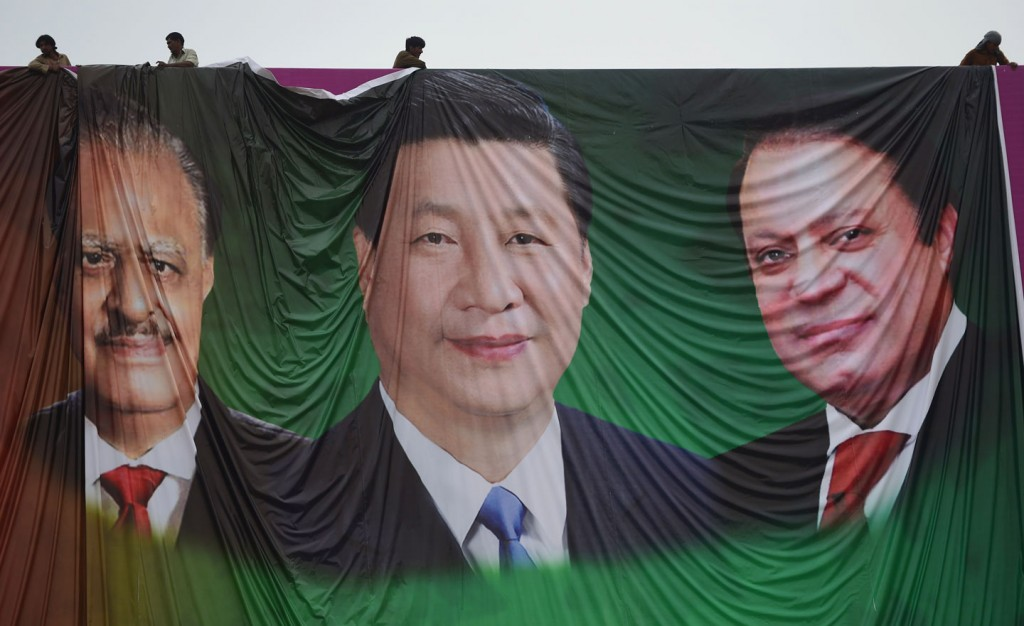 """Pakistani labourers arrange a welcoming billboard featuring pictures of visiting Chinese President Xi Jinping (C) and his Pakistani counterpart Mamnoon Hussain (L) and Prime Minister Nawaz Sharif (R) in Islamabad on April 18, 2015. Pakistan needs a """"huge amount of financing"""" for infrastructure and energy projects and China is ready to announce help when President Xi Jinping visits next week, a foreign ministry official said April 17, 2015. AFP PHOTO / Farooq NAEEM        (Photo credit should read FAROOQ NAEEM/AFP/Getty Images)"""