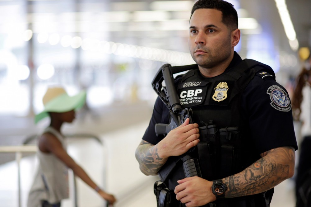 A U.S. Customs and Border Protection officer patrols outside of the departures area at Miami International Airport, Friday, July 1, 2016, in Miami. There is increased security at the airport on this Independence Day holiday weekend after Tuesday's terrorist attacks at Istanbul's Ataturk International Airport. (AP Photo/Lynne Sladky)