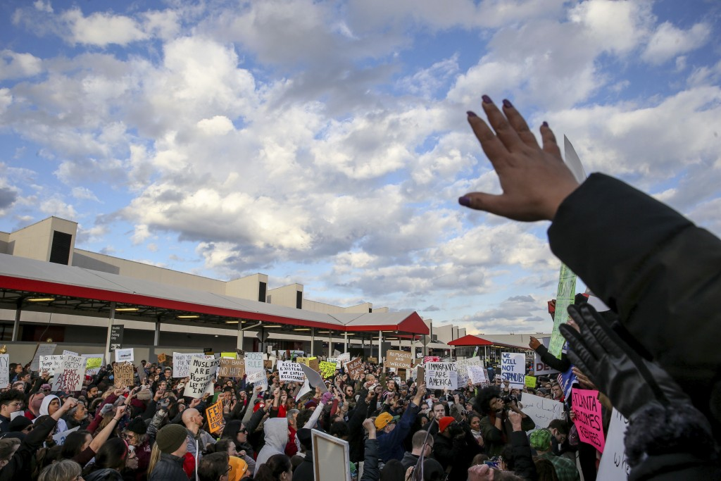 Demonstrators hold signs and chant at Hartsfield-Jackson International Airport during a demonstration to denounce President Donald Trump's executive order that bars citizens of seven predominantly Muslim-majority countries from entering the U.S., Sunday, Jan. 29, 2017, in Atlanta. (AP Photo/Branden Camp)