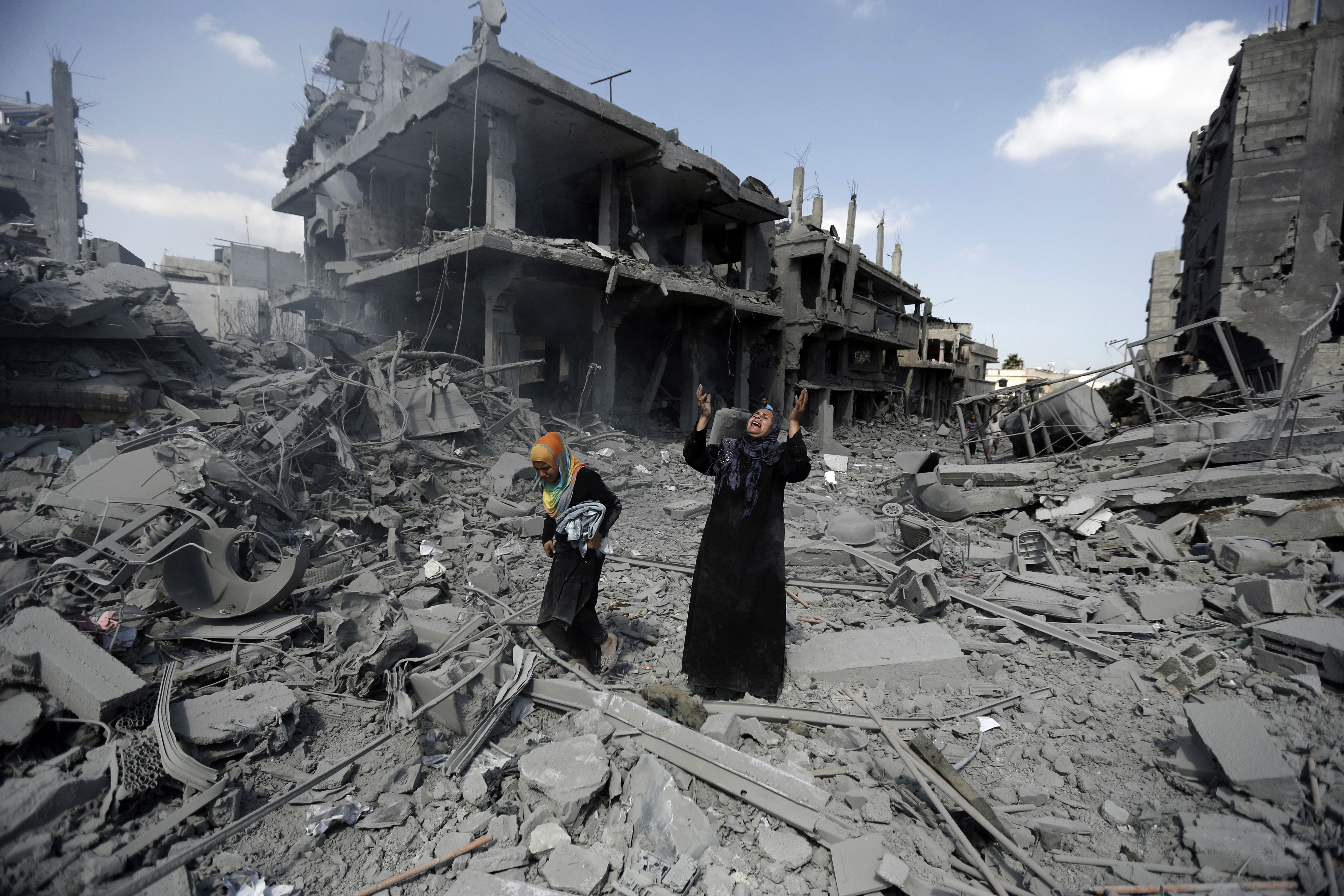 A Palestinian woman pauses amid destroyed buildings in the northern district of Beit Hanun in the Gaza Strip during an humanitarian truce on July 26, 2014. The bodies of at least another 35 Palestinians were recovered from rubble across Gaza during a truce, raising to over 900 the overall death toll of Israel's onslaught on the territory since July 8, medics said. AFP PHOTO / MOHAMMED ABED        (Photo credit should read MOHAMMED ABED/AFP/Getty Images)