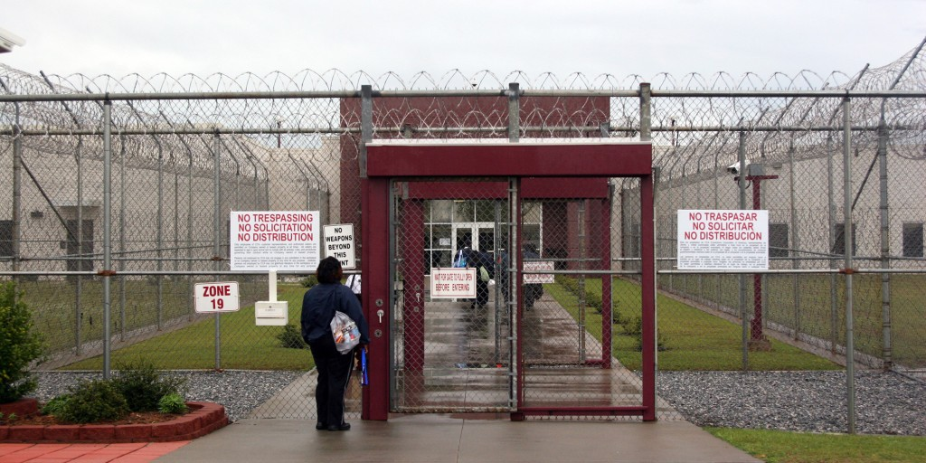 FILE - In this April 13, 2009, file photo, an employee waits at the front gate of the Stewart Detention Facility, a Corrections Corporation of America immigration facility in Lumpkin, Ga. CCA, the largest contractor for U.S. Immigration and Customs Enforcement, reached a preliminary agreement in May, 2010, to soften confinement, free of charge, at nine immigrant facilities covering more than 7,100 beds. ICE officials see the deal, which includes Stewart, as a precursor to changes elsewhere. (AP Photo/Kate Brumback, File)