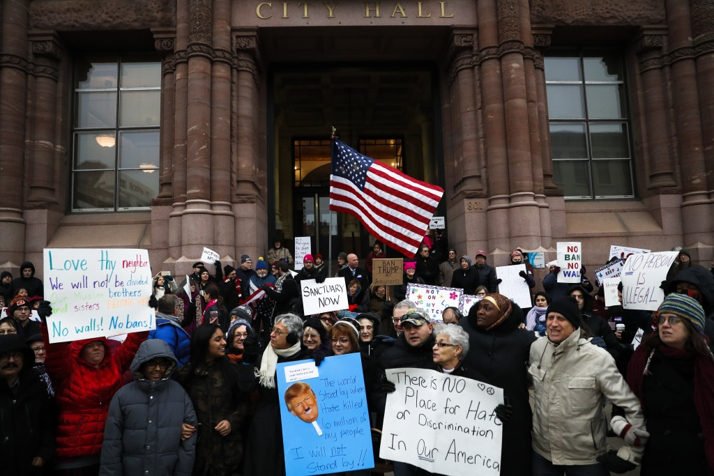 "Demonstrators gather in solidarity against President Donald Trump's executive order temporarily banning immigrants from seven Muslim-majority countries from entering the U.S. and suspending the nation's refugee program Monday, Jan. 30, 2017, outside City Hall in Cincinnati. In addition, earlier in the day Mayor John Cranley declared Cincinnati a ""sanctuary city,"" meaning city will not enforce federal immigration laws against people who are here illegally, in keeping with current policy. (AP Photo/John Minchillo)"