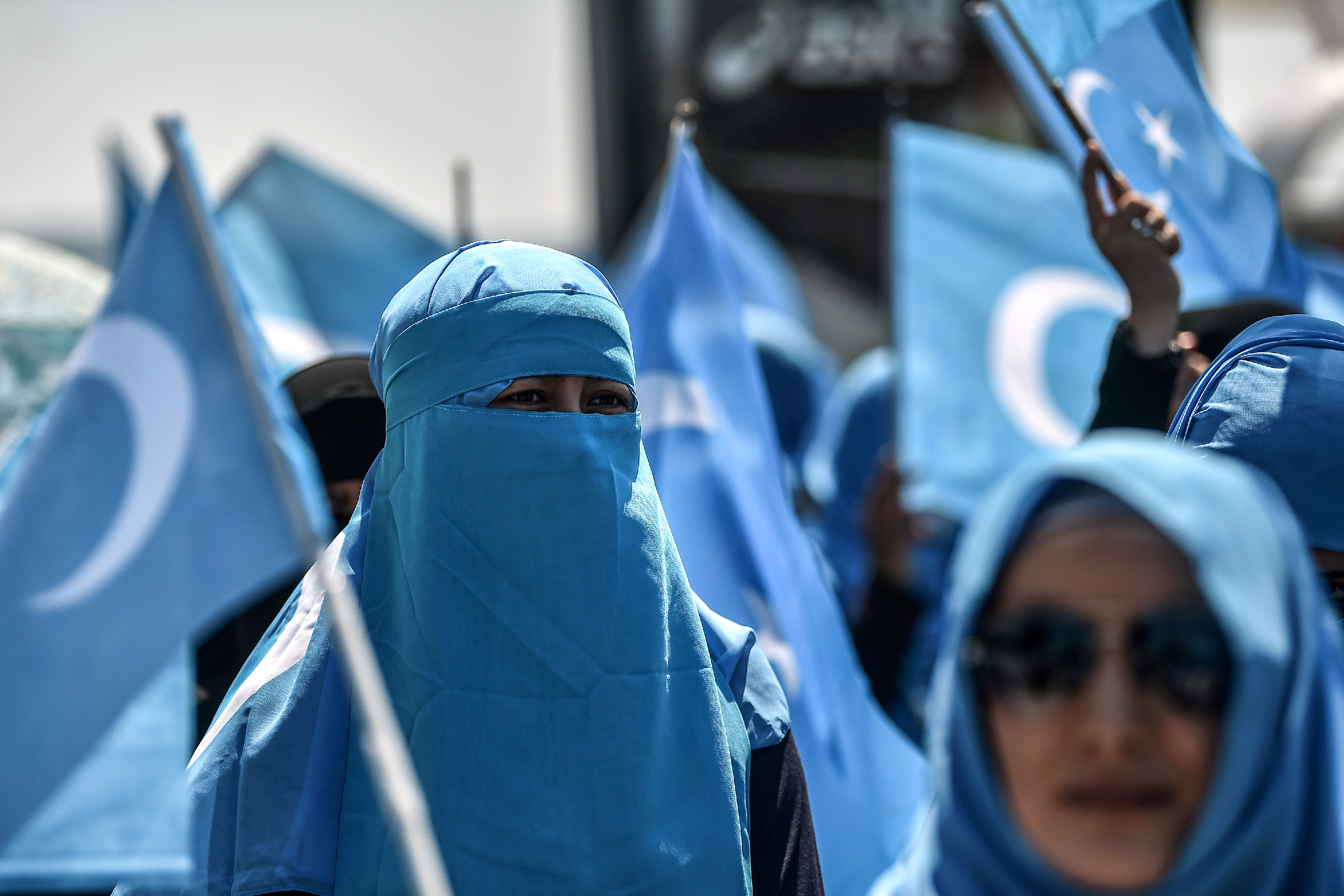 Demonstrators waving the flag of East Turkestan attend a protest of supporters of the mostly Muslim Uighur minority and Turkish nationalists to denounce China's treatment of ethnic Uighur Muslims during a deadly riot in July 2009 in Urumqi, in front of the Chinese consulate in Istanbul, on July 5, 2018. - Nearly 200 people died during a series of violent riots that broke out on July 5, 2009 over several days in Urumqi, the capital city of the Xinjiang Uyghur Autonomous Region, in northwestern China, between Uyghurs and Han people. (Photo by OZAN KOSE / AFP)