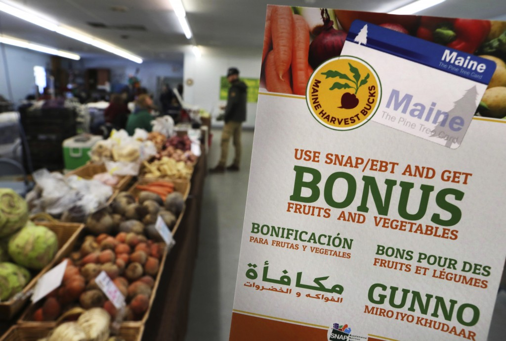 FILE - In this Friday, March 17, 2017, file photo, a sign advertises a program that allows food stamp recipients to use their EBT cards to shop at a farmer's market in Topsham, Maine. A proposal to curtail the nation's food stamp program would pinch families struggling to pay for groceries and ripple through other areas of the economy, including supermarkets and discounters. (AP Photo/Robert F. Bukaty, File)