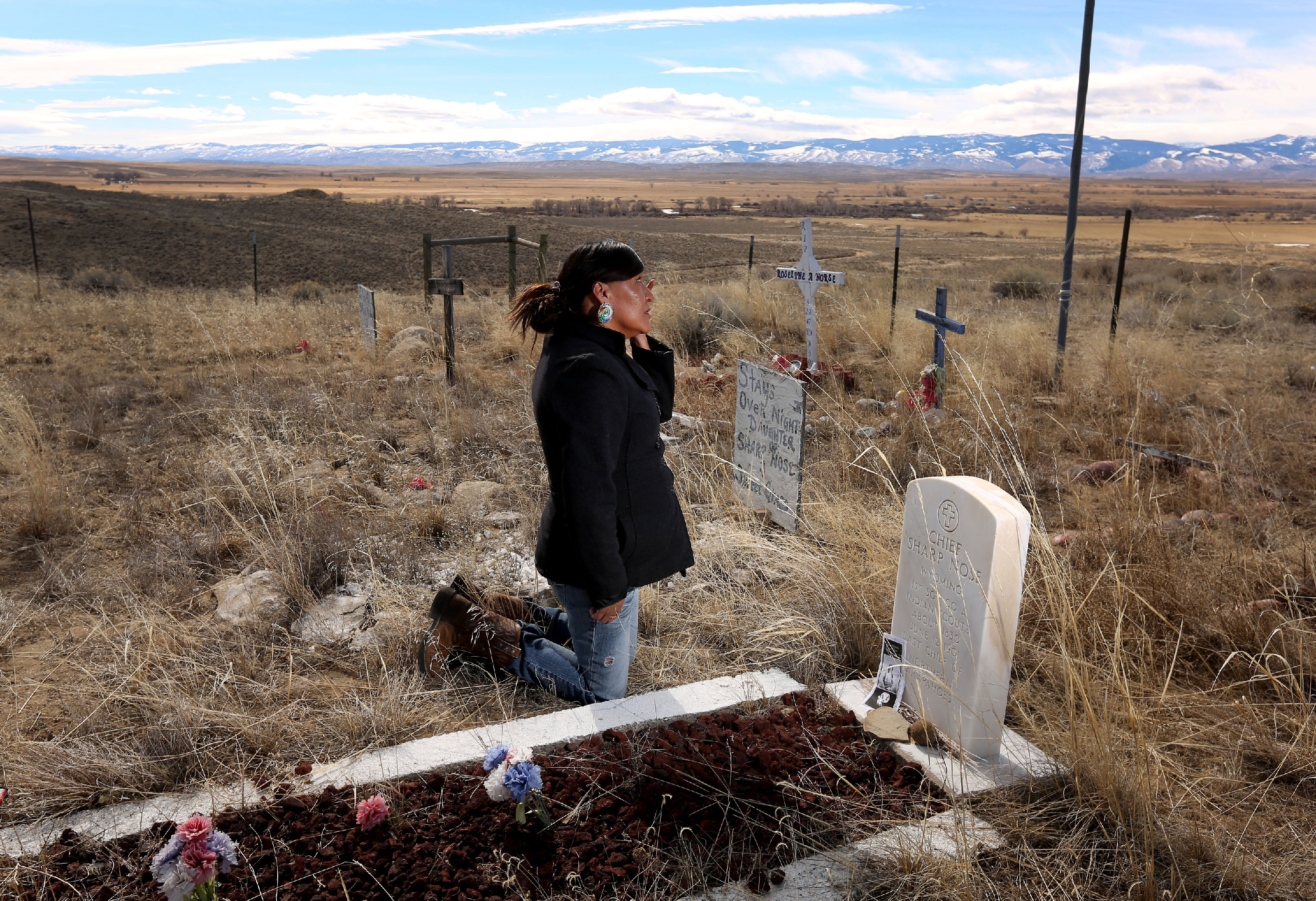 ADVANCE FOR WEEKEND EDITIONS - In this March 1, 2016 photo, Yufna Soldier Wolf wipes away tears while kneeling at the grave of her great-grandfather, Chief Sharp Nose of the Northern Arapaho Tribe, at the family cemetery on the Wind River Reservation near Riverton, Wyo. Soldier Wolf is seeking the remains of her great-uncle Little Chief, who died while attending Carlisle Indian School in Carlisle, Pennsylvania. (Dan Cepeda/The Casper Star-Tribune via AP) MANDATORY CREDIT
