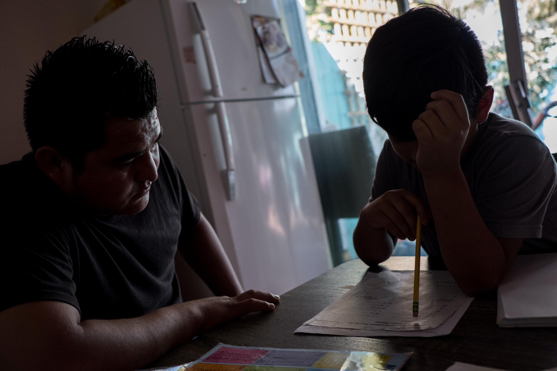 Carlos Rueda Cruz, 28, left, helps his son Brian Josue, 9, with his homework at their home in Sacramento, Calif., Monday, Sept. 10, 2018. (Joel Angel Juárez for The Intercept)