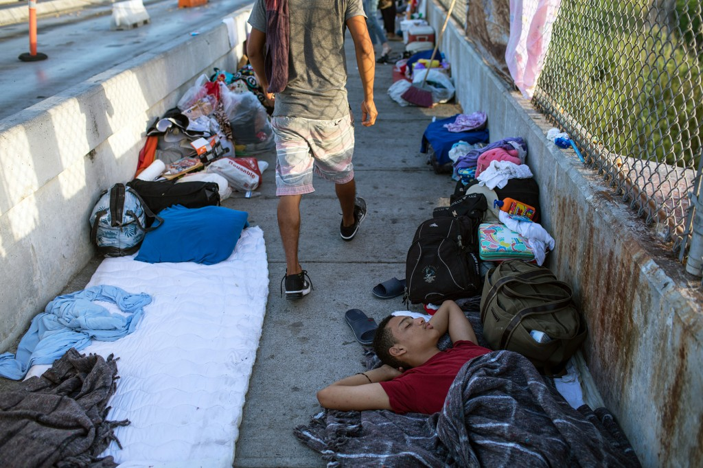 MATAMOROS, MX - JUNE 28: A 14-year-old boy from Honduras sleeps on the Mexican side of the Brownsville & Matamoros International Bridge, where he and his family have been waiting for days after being denied entry into the U.S., on June 28, 2018 near Brownsville, Texas. Despite the Trump administration ending the zero-tolerance policy toward immigration, attention remains focused on the U.S.-Mexico border where migrants from Central America continue to arrive on a daily basis. (Photo by Tamir Kalifa/Getty Images)