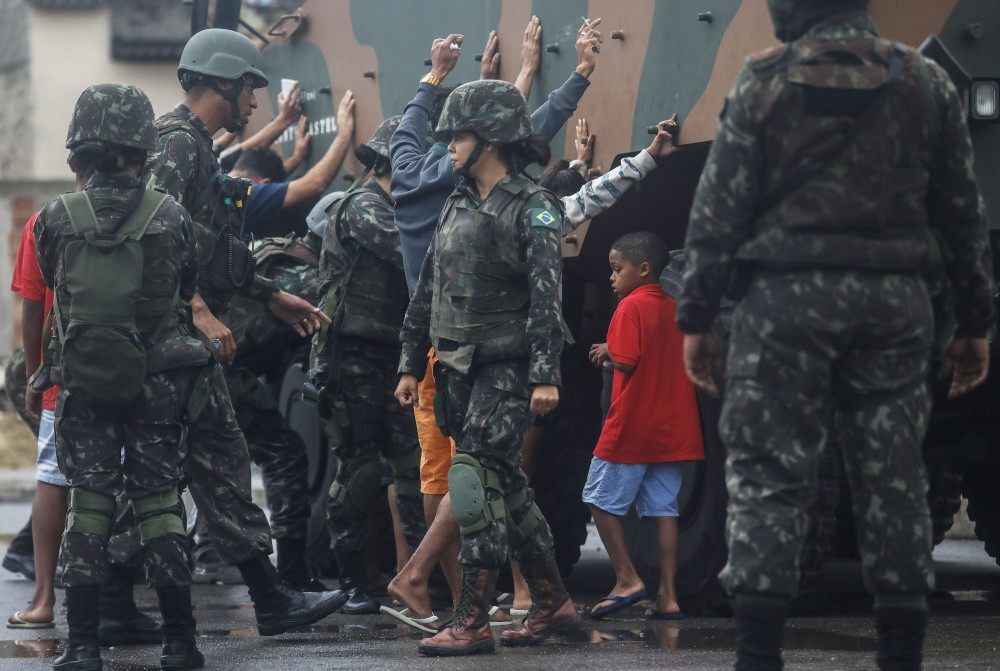 RIO DE JANEIRO, BRAZIL - AUGUST 21: A boy waits as Brazilian soldiers search adults during a 'Mega Operation' conducted by the Brazilian Armed Forces along with police against gang members in seven of Rio's most violent 'favela' communities on August 21, 2017 in Rio de Janeiro, Brazil. The children were waiting for adults to be searched nearby as many 'favela' residents were searched both entering and departing the communities during the operation. Brazil has deployed 8,500 members of the armed forces to Rio in an attempt to increase security amidst a spike in violence and crime. In the first six months of 2017 there were 3,457 homicides in Rio state, the highest level of violence seen there since 2009. (Photo by Mario Tama/Getty Images)