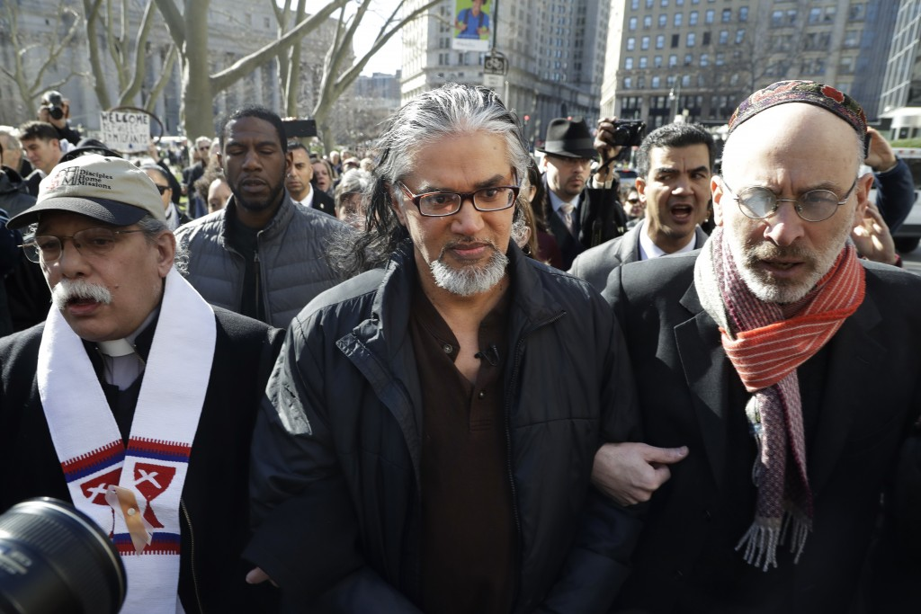 Ravi Ragbir, center, executive director of the New Sanctuary Coalition, walks with hundreds of supporters as he arrives for his annual check-in with Immigration and Customs Enforcement, Thursday, March 9, 2017, in New York. The Trinidadian immigrant works with an interfaith network of congregations and activists working to protect New York's immigrant families from detention and deportation. Ragbag says he could face deportation. (AP Photo/Mark Lennihan)