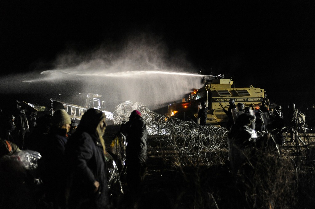 Police use a water cannon on protesters during a protest against plans to pass the Dakota Access pipeline near the Standing Rock Indian Reservation, near Cannon Ball, North Dakota, U.S. November 20, 2016. REUTERS/Stephanie Keith - D1BEUOBKNBAA