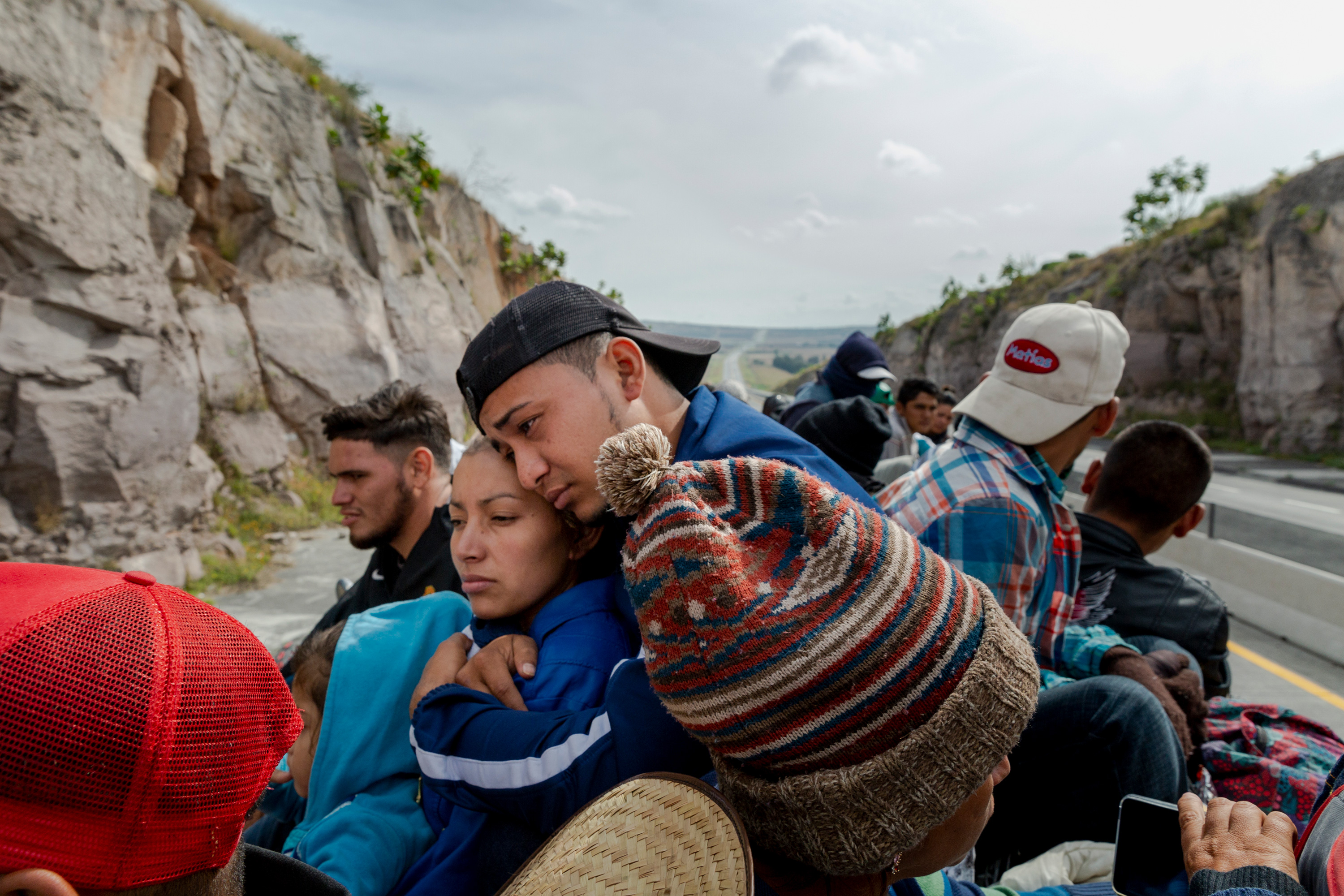 Aldo Ivan, 18 from Guatemala and Griselda, 22 from Honduras embrace on top of a cargo truck heading north bound towards Guadalajara on November 12, 2018 where they will stay overnight at a temporary migrant shelter set up by the Mexican government on their way to their Tijuana destination on the first migrant caravan. Photographer: Mark Abramson
