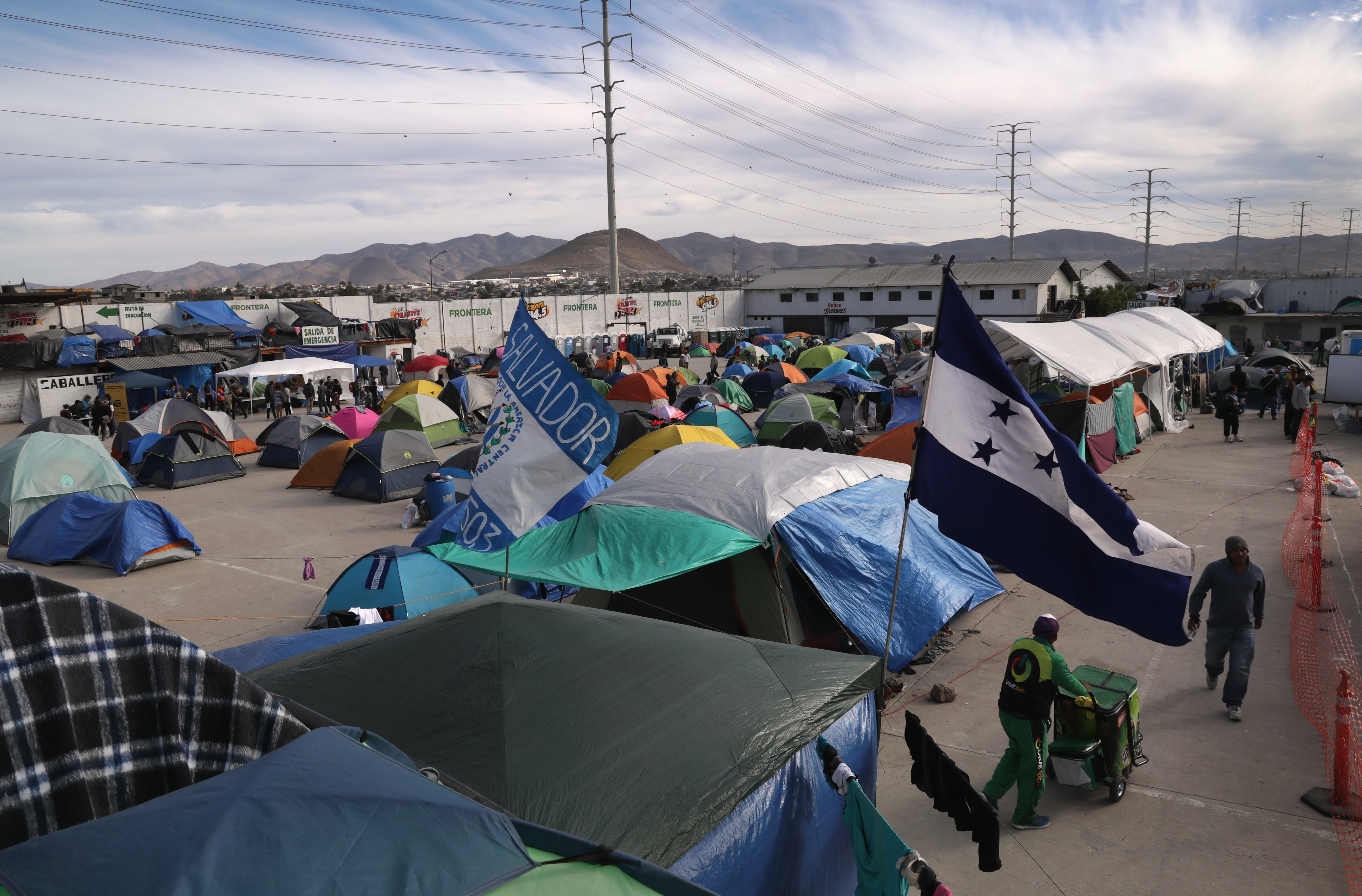 TIJUANA, MEXICO - DECEMBER 04:  Honduran and Salvadorian flags fly over the Barretal migrant caravan camp on December 4, 2018 from Tijuana, Mexico. After traveling more than 6 weeks from Central America, thousands of immigrants remain in Tijuana, many awaiting asylum interviews and others deciding whether to cross illegally into the United States. (Photo by John Moore/Getty Images)