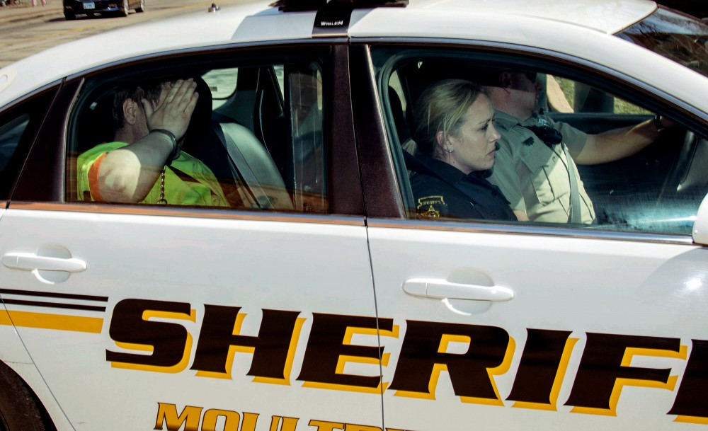 Moultrie County Sheriff deputies transport Michael McWhorter to the Federal Courthouse in Urbana, Ill., Wednesday March 21, 2018. McWhorter is one of three suspects arrested last week on charges of carry out the Aug. 5 pipe-bomb assault on the Dar Al-Farooq Islamic Center in Bloomington, Minnesota. (Rick Danzl/The News-Gazette via AP)