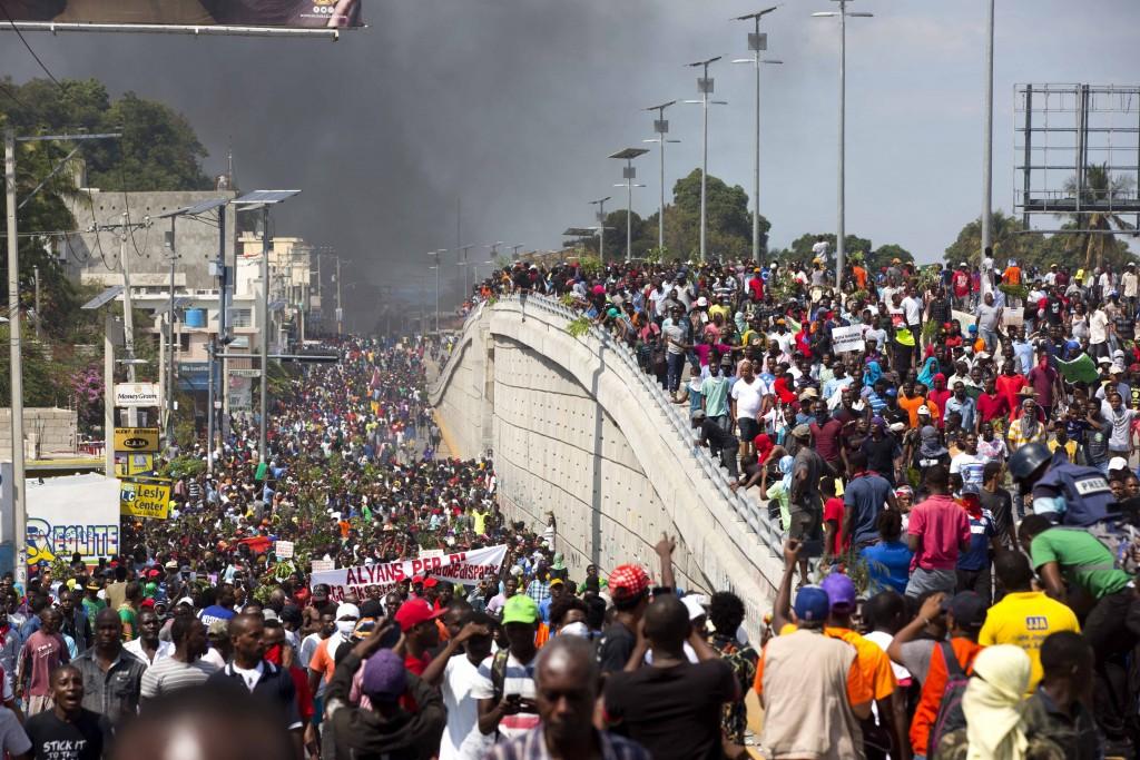 Milhares de manifestantes marcham nas ruas durante protesto para exigir a renúncia do presidente Jovenel Moïse em 7 de fevereiro.