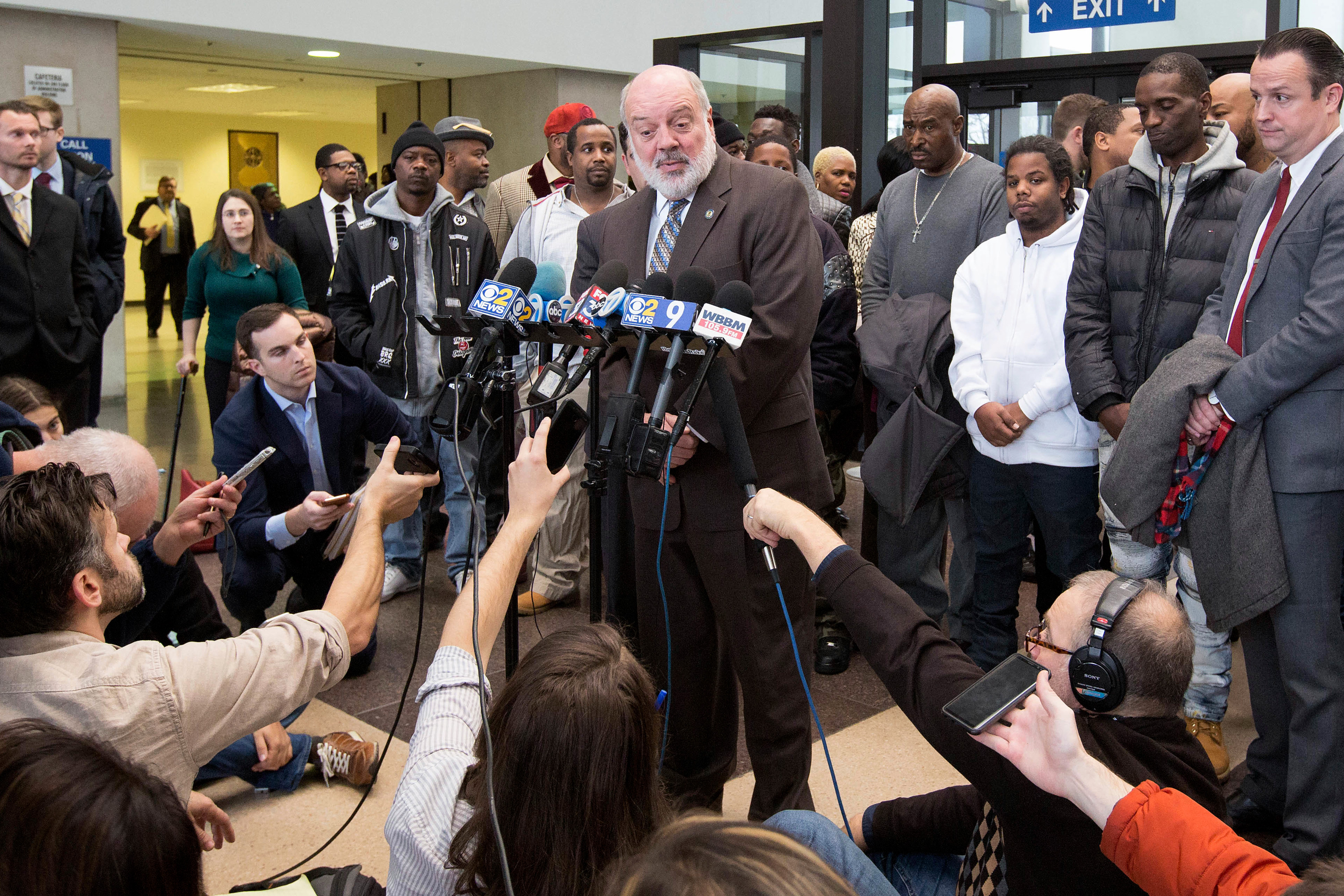 Mark Rotert, head of the conviction integrity unit of the Cook County State's Attorney's Office, talks to reporters Thursday, Nov. 16, 2017, in Chicago, after a judge in Chicago threw out the convictions of 15 men, some of whom are standing behind him, who say a corrupt Chicago police sergeant manufactured evidence that sent them to prison. Cook County prosecutors made the request Thursday as 10 of the men stood before Judge Leroy Martin Jr. It was the latest chapter in a scandal that resulted in former Sgt. Ronald Watts' 2013 conviction for extorting money from drug dealers. (AP Photo/Teresa Crawford)