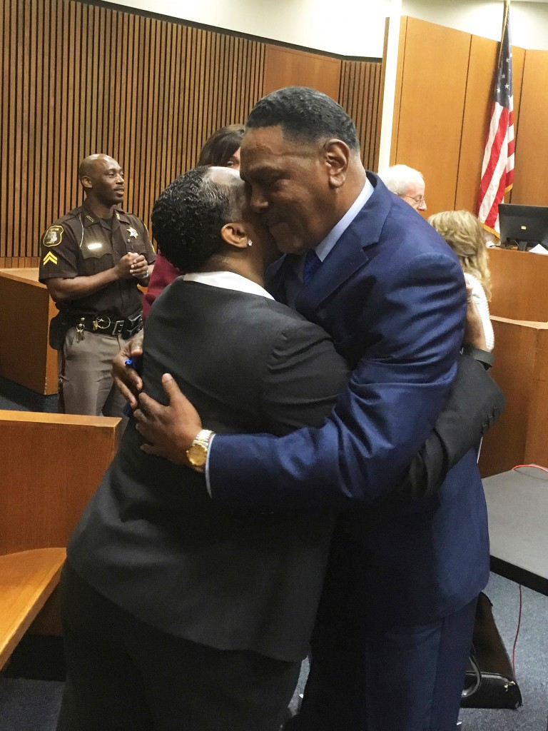 Richard Phillips, right,  hugs Det. Patricia Little in a Wayne County, Mich., courtroom on Wednesday, March 28, 2018, in Detroit. Phillips, a Michigan man whose murder conviction was thrown out after he spent 45 years in prison will not face a second trial. (AP Photo/Ed White)