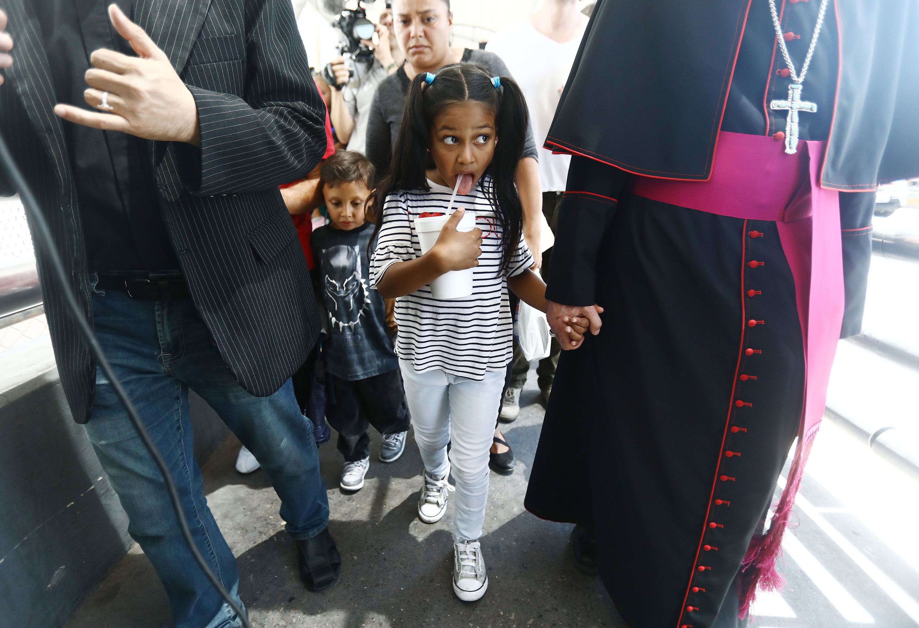 El Paso Bishop Mark Seitz (R) escorts Celsia Palma (C), 9, from Honduras, as they cross the Paso Del Norte Port of Entry bridge towards the U.S. on June 27, 2019, in Ciudad Juarez, Mexico. Seitz escorted Celsia and other family members across the port of entry to be processed by U.S. immigration authorities. Earlier, Seitz and clergy from the Diocese of Ciudad Juarez held a prayer with migrants who were recently returned to Ciudad Juarez from El Paso because of the controversial 'Remain in Mexico' policy.