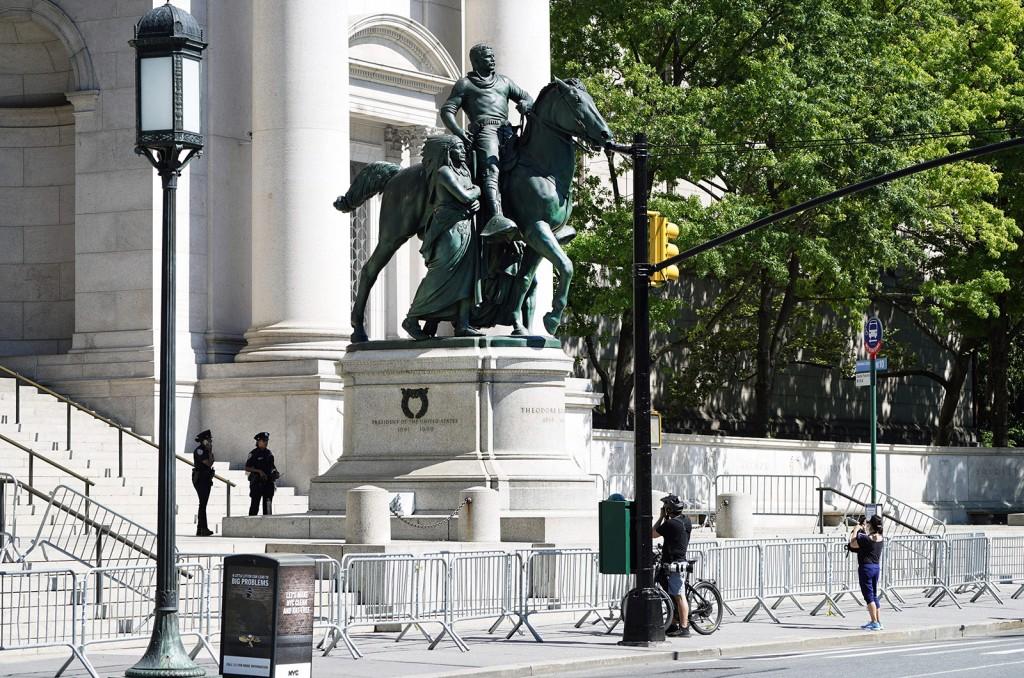 Pessoas passam pela estátua equestre de Theodore Roosevelt em frente ao Museu Americano de História Natural, em 22 de junho, na cidade de Nova York.