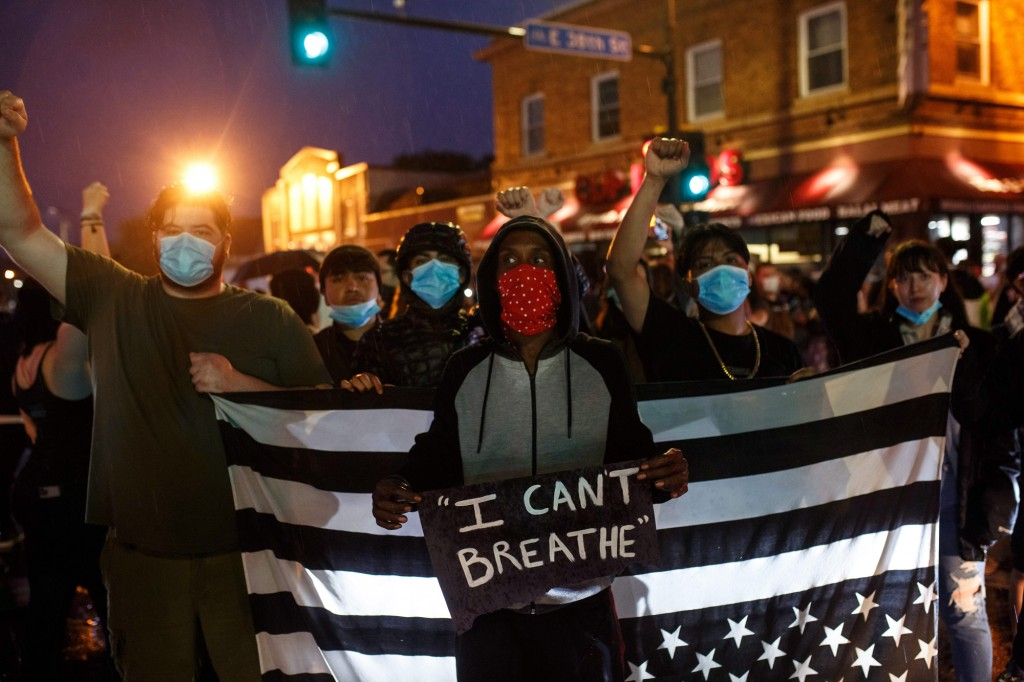 Manifestantes levantam os punhos durante protesto próximo ao local onde George Floyd morreu sob custódia da polícia, no dia 26 de maio, em Minneapolis, Minnesota.