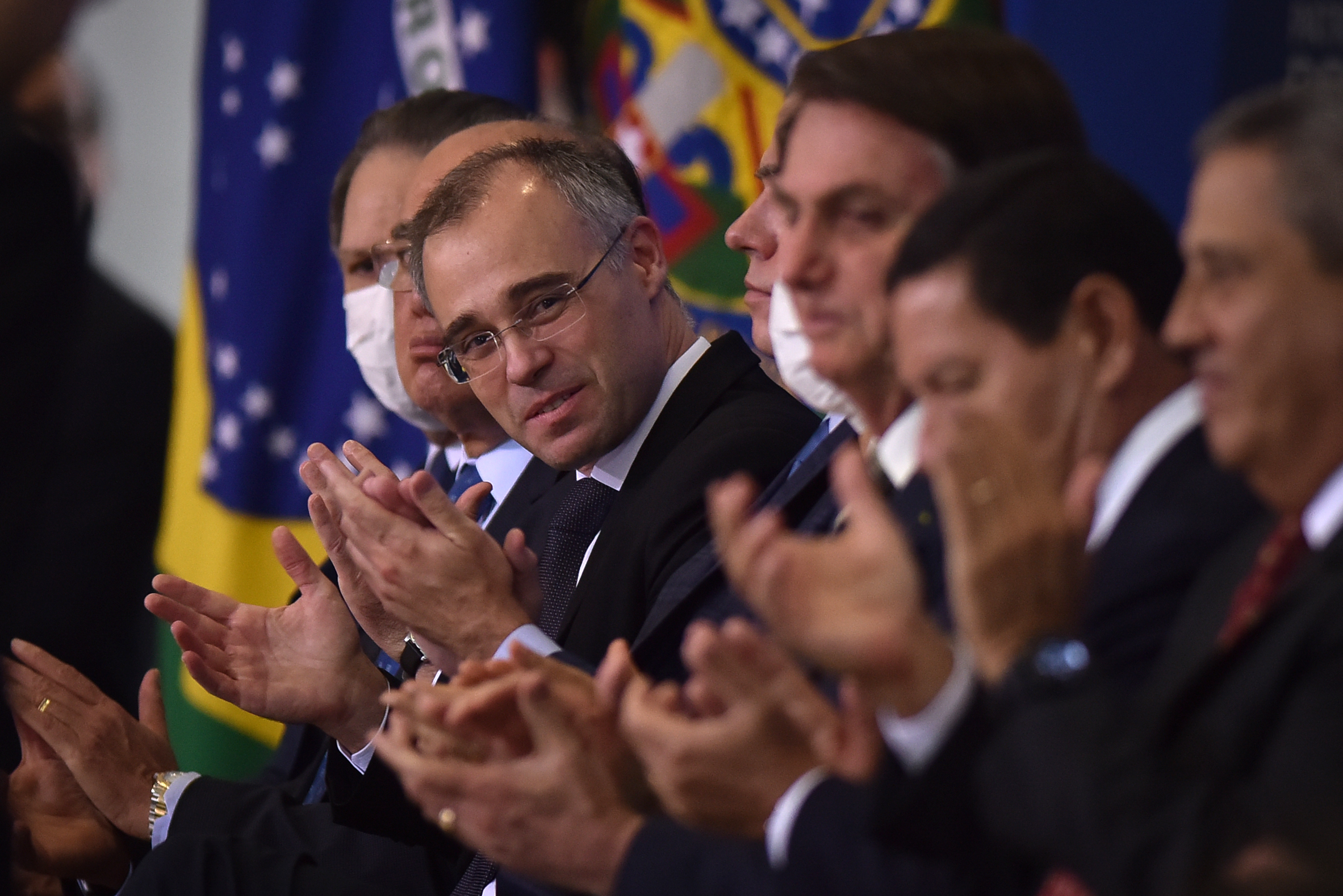 Andre Mendonca, Brazil's new minister of justice, center, applauds during an inauguration ceremony with Jair Bolsonaro, Brazil's president, at Planalto Palace in Brasilia, Brazil, on Wednesday, April 29, 2020. Medonca is taking over after Sergio Moro quit the post following Bolsonaro's firing of the federal police chief. Photographer: Andres Borges/Bloomberg via Getty Images
