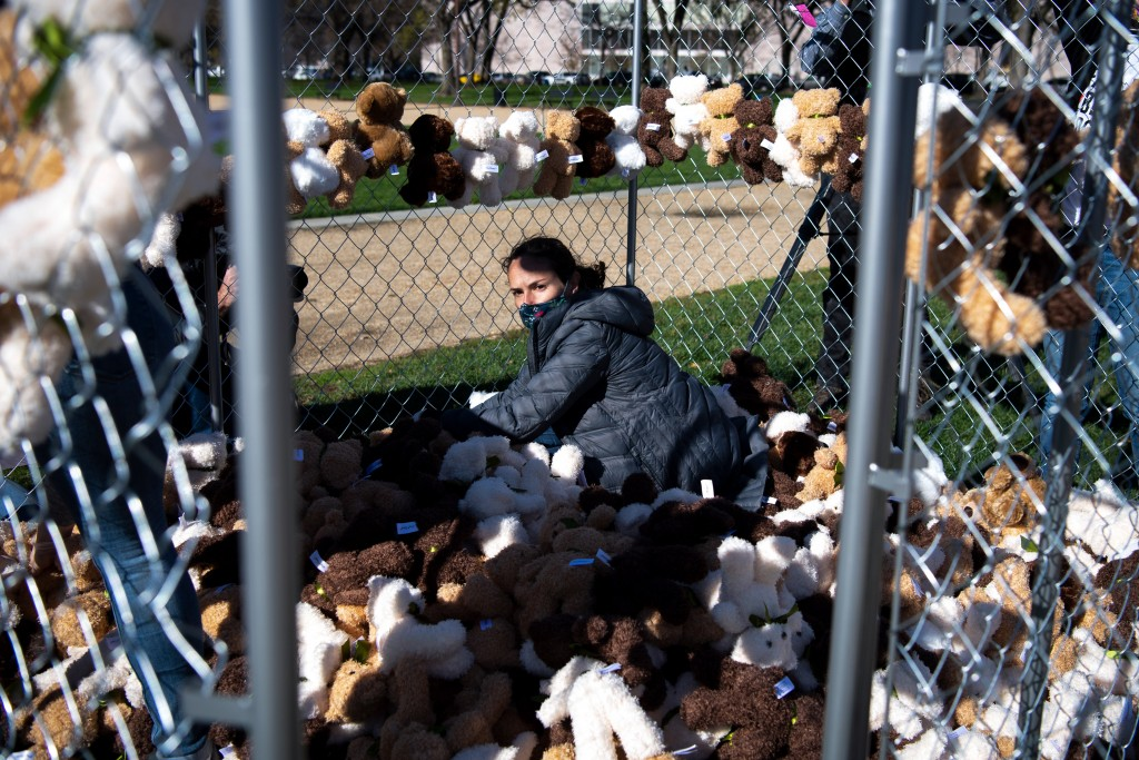 """Lisa Watkins, a volunteer from Families Belong Together, places teddy bears inside a cage as part of a demonstration involving 600-plus teddy bears meant to represent the children still separated as a result of U.S. immigration policies"""" in Washington on Monday, Nov. 16, 2020. (Photo by Caroline Brehman/CQ-Roll Call, Inc via Getty Images)"""